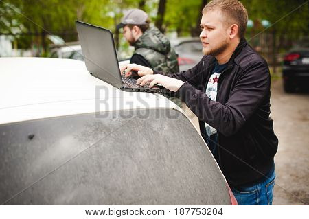 Man With A Laptop In Parking Lot In Yard Near Car Is Doing Manipulations With Cyber System, Concept