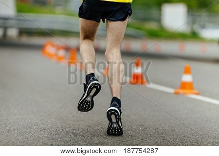 male feet in running shoes in road dark asphalt with traffic cones safety