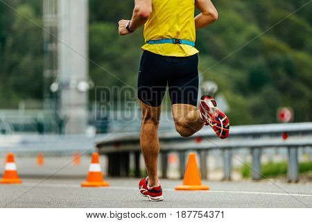 one male athletic runner running in roads with traffic cones safety