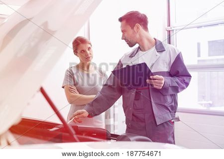 Young male engineer explaining car engine to female customer in workshop