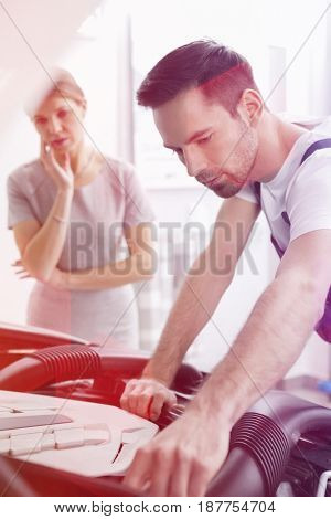 Young male technician examining car engine with worried customer in background at workshop