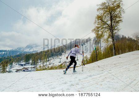 female athlete with trekking poles on background snowy mountains
