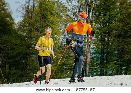 Rosa Khutor Russia - May 4 2017: two runners men running snowy trail with trekking poles in race Vertical kilometer