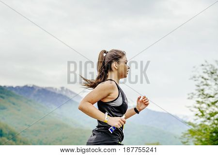 Rosa Khutor Russia - May 7 2017: young girl runner with energy nutrient gel in hand running in race Spring mountain marathon