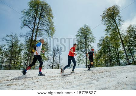 Rosa Khutor Russia - May 4 2017: three men runners running snowy mountain trail in race Vertical kilometer