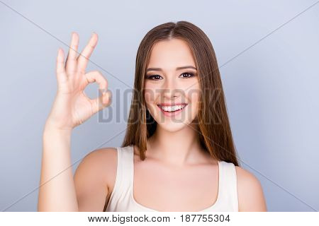 Cheerful Young Girl On The Pure Light Blue Background Is Smiling, Wearing A White Casual Singlet And
