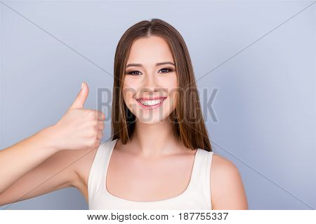 Close Up Of Young Gorgeous Girl Standing On The Pure Light Blue Background And Smiling, Wearing A Wh