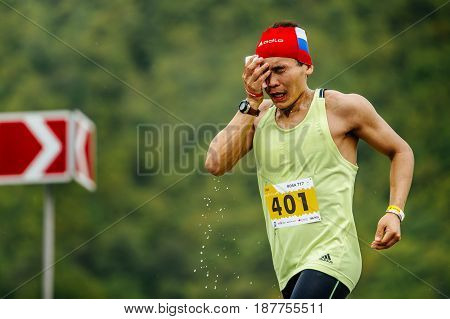 Rosa Khutor Russia - May 7 2017: young man runner on water point in hand sponge with water in race Spring mountain marathon