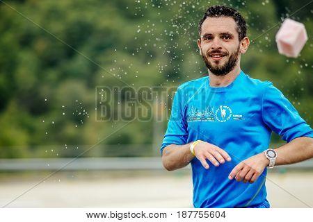 Rosa Khutor Russia - May 7 2017: man runner on water point throws sponge splashing water in race Spring mountain marathon