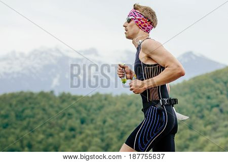 Rosa Khutor Russia - May 7 2017: young man runner with energy nutrient gel in hand running in race Spring mountain marathon