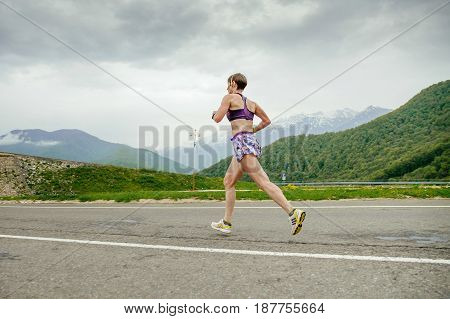 Rosa Khutor Russia - May 7 2017: woman middle-aged runner running on asphalt road in race Spring mountain marathon