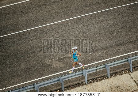 Rosa Khutor Russia - May 7 2017: view from top male runner running on dark asphalt road in race Spring mountain marathon