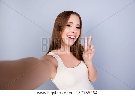 Carefree And Happy, Funky Mood. Cute Young Smiling Girl Is Making Selfie On A Camera. She Is Wearing