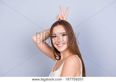 Fun Time! Young Attractive Girl In White Casual Singlet Is Standing On Pure Background And Is Foolin
