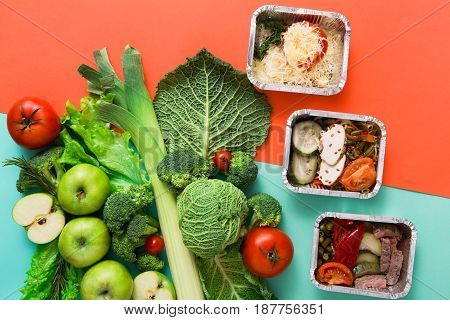 Healthy meals in lunch boxes with green vegetables and fruits. Diet, detox and healthy food concept - top view flat lay on bright background. Ingredients for salad