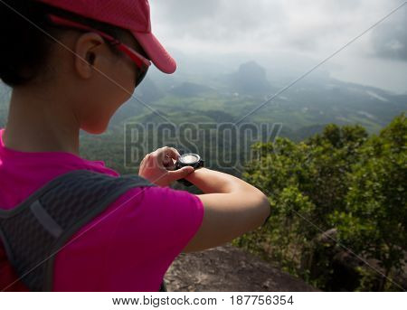 young womanhiker checking the altimeter on seaside mountain peak