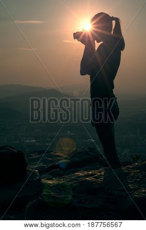 Silhouette of a young girl taking pictures,