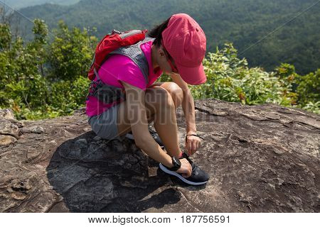 Young female trail runner tying shoelace on mountain peak