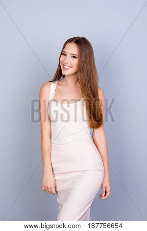 Young Slim Cute Girl In White Elegant Dress. She Is Successful And Beautiful. Behind Is A Pure Backg
