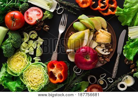 Eating healthy vegetable food on black background. Fresh organic peppers, tomato, cabbage and other meals with empty plate, copy space