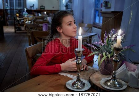 Teenage girl in red sits at table with two burning candles in cafe.