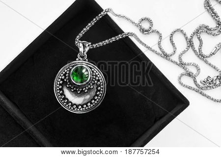 Vintage silver emerald medallion in jewel box closeup