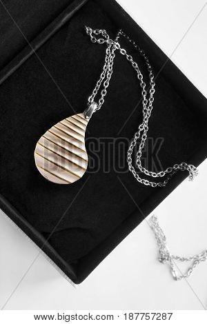 Golden petal pendant on silver chain in jewel box closeup