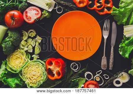 Healthy vegetable food on black background. Fresh organic peppers, tomato, cabbage and other meals with empty orange plate, copy space