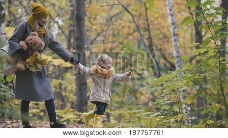 Little daughter with her mommy and Taddy bear walks in autumn park - plays the leaves, telephoto