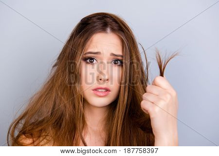 Close Up Cropped Portrait Of Surprised Upset Young Lady With Damaged Ends Of Her Hair In Her Arm, Is