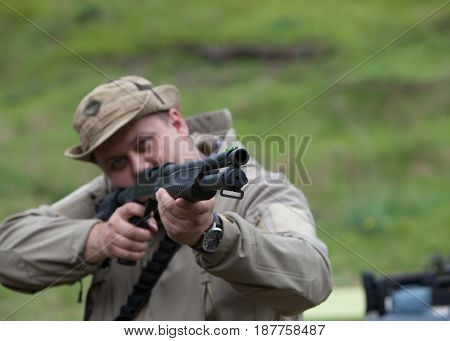 Hunter with a gun. Standing in the forest and waiting for prey.