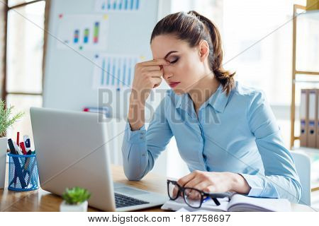 Portrait Of Tired Businesswoman Having Headache At Workplace After Working With Computer For A Long