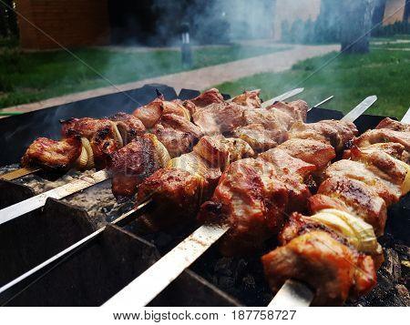 Marinated shashlik preparing on a barbecue grill over charcoal. Shashlik or Shish kebab popular in Eastern Europe. Shashlyk skewered meat was originally made of lamb. Roast Beef Kebabs On BBQ Grill.
