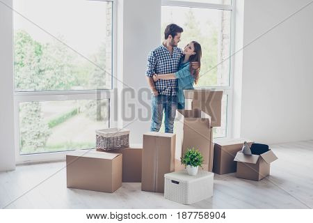 Successful Young Couple Is Moving To New Nice Place And Embracing, Around Are Carton Boxes With Thei