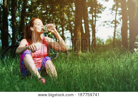 Sports Woman Sitting On The Green Grass And Drinks Water