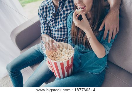 Cropped Close Up Top View Photo Of Young Beautiful Couple, Which Is At Home, Eating Popcorn From A B