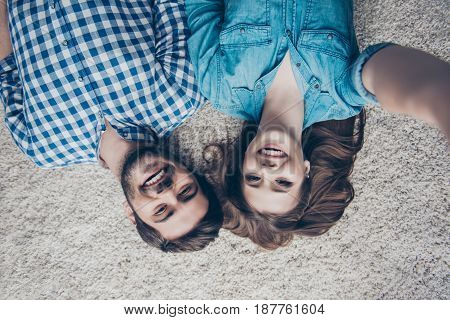 Upside Down Top View Photo Of Two Young Friends, Who Are Taking Selfie And Smiling. They Lie On The