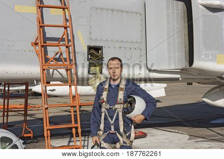 Military Pilot With Helmet In His Hand Standing Near A Jet Plane