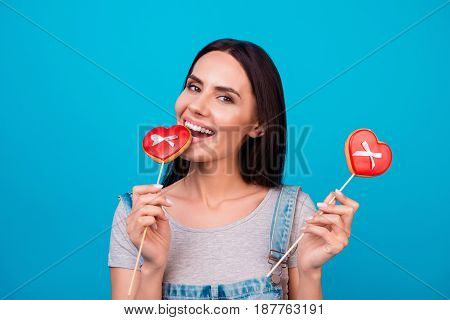 Yummy! Charming Young Brunette With Red Candies Hearts On Bright Blue Background In Casual Outfit. S