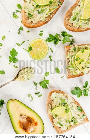 Homemade Sandwich Toasts With With Guacamole, Lime Lemon And Parsley On White Table, Copy Space Top