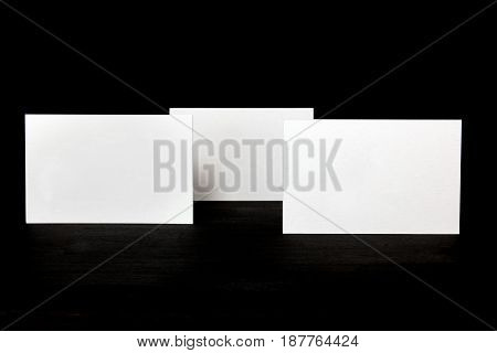 A photo of blank white thick cardboard business cards on a black background texture. A mockup or a minimalist banner with copyspace
