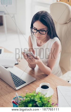 Close Up Top View Of Young Brunette Woman Typing An Sms On Her Pda While Having A Coffee Break At Wo