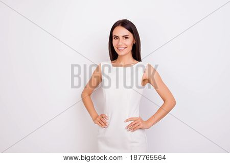 Portrait Of Slim Cute Girl In White Smart Clothes With Her Hands On The Hips. She Is Successful And