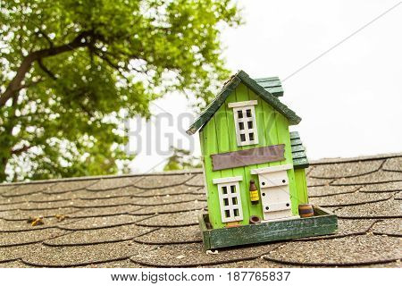Wooden model of a family house on the asphalt roof. Mortgage sale for building a house
