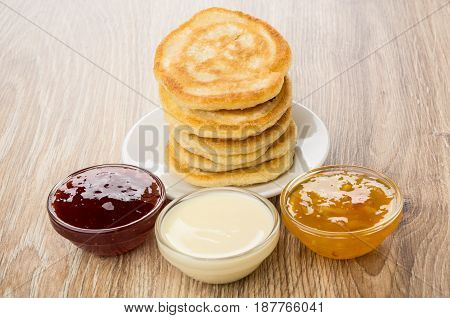 Stack Of Pancakes In Saucer And Transparent Bowls With Jams