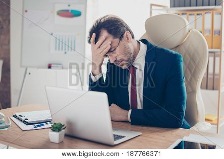 Depressed Entrepreneur Realtor Is Holding His Head With Hand, He Is Tired And Frustrated, Sitting In