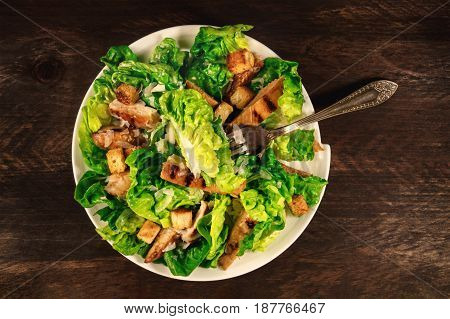 An overhead photo of a plate of chicken Caesar salad with a fork, on a dark rustic background with a place for text