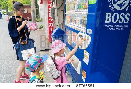 Tokyo; Japan - May 1; 2017: Family are buying soft drink cans from coin vendors.