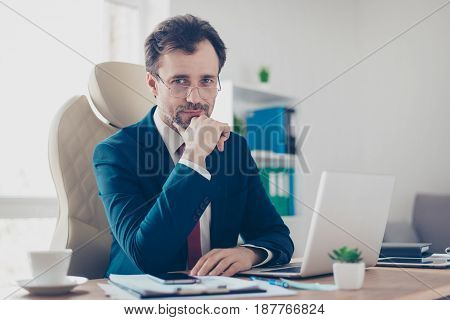 Smiling Businessman Banker Is Sitting At His Workplace And Looking In Camera. He Is Wearing Formalwe