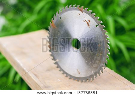 Circular saw blade disk with wooden beam.